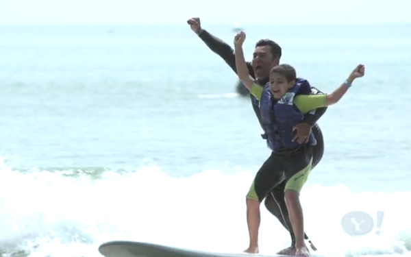 Surfer helping autistic boy